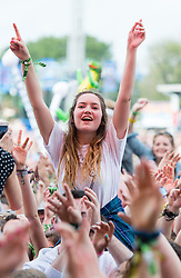 © Licensed to London News Pictures. 13/06/2015. Isle of Wight, UK.  Festival goers on their friends shoulder watch James Bay perform at Isle of Wight Festival 2015 on a warm sunny Saturday Day 3.  Yesterday suffered torrential rain all afternoon and evening, after a first day of warm sun.  This years festival include headline artists the Prodigy, Blur and Fleetwood Mac.  Photo credit : Richard Isaac/LNP
