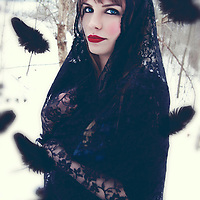 Photograph of a young caucasian woman with blonde hair, striking blue eyes, and red lipstick. She is covered with a black lace shawl and standing in a wooded area that is blanketed in snow. She is smiling at the camera with black feathers surounding her.