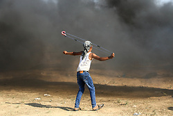 July 6, 2018 - Gaza, Palestine - A young Palestinian throwing a swallow back to the forces..Protest against the recognition of Jerusalem as the capital of Israel that resulted into injuries among Palestinian citizens who were fired with live bullets and tear gas canisters by the Zionist occupation forces on the border of the Gaza Strip near the site of Nahal Oz east of Gaza City. (Credit Image: © Ahmad Hasaballah/SOPA Images via ZUMA Wire)