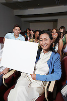 Female teacher holding blank board, in front of class, portrait