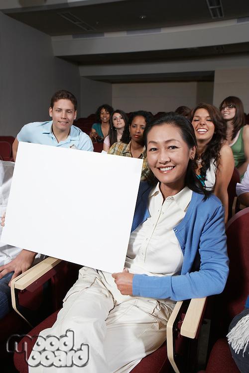 Female teacher holding blank board, in front of class, portrait