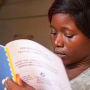 LÉGENDE: Edem revise son rapport de stage devant la porte de sa chambre. LIEU: CERFER, Lomé, Togo. PERSONNE(S): Alema Edem Djagbo (à droite).