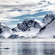 Rugged rocky mountains rise up sharply on the shore of the Antarctic Peninsula near Cuverville Island.