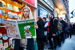 © Licensed to London News Pictures. 16/01/2015. LONDON, UK. Amelia Wightwick reading a copy of Charlie Hebdo's survival edition after buying it from 'La Page' book shop in London on Friday, 16 January 2015. Photo credit : Tolga Akmen/LNP