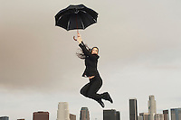 Woman jumping with umbrella mid-air above city
