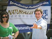 Volunteer Sarah Little, left, watches as president and co-founder of Naturally Blue PAC Nate Looney waves on Saturday, March 17, 2012 at Bulldog Stadium in Springdale, Ark. (Photo by Beth Hall)
