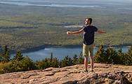Acadia National Park, Maine--September 21, 2016. A man stands with arms outstretched looking over the scenery from a peak of Cadillac Mountain in Maine.