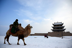 A staff member on a camel passes a city wall in the Jiayu Pass scenic spot after snowfall in Jiayuguan City, northwest China's Gansu Province, December 21, 2012. Photo by Imago / i-Images...UK ONLY