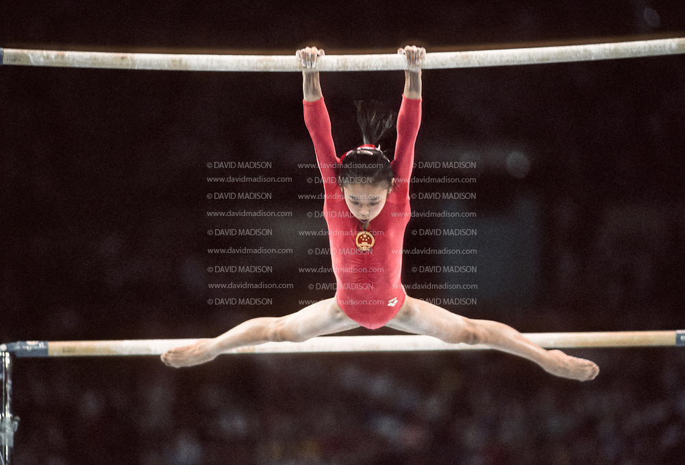 SEATTLE - JULY 1990:  Li Li of China competes in the uneven bars event of the gymnastics competition of the 1990 Goodwill Games held from July 20 - August 5, 1990.  The gymnastics venue was the Tacoma Dome in Tacoma, Washington.  (Photo by David Madison/Getty Images)