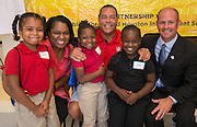 Paula Harris, Kelvin Sampson and Doug Hall pose for a photograph with students during the Read for the NCAA Final Four kick-off at Blackshear Elementary School, September 24, 2015.