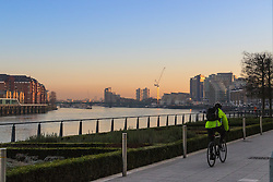 London, February 24th 2016. A cyclist rides along the Thames as the sun rises on a chilly but clear morning in London. &copy;Paul Davey<br /> FOR LICENCING CONTACT: Paul Davey +44 (0) 7966 016 296 paul@pauldaveycreative.co.uk