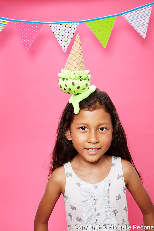 Young hispanic girl wearing mint chocolate chip ice cream cone hat against a pink seamles<br /> Photographed at Photoville Photo Booth September 20, 2015