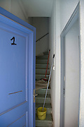 residential stairwell with two brooms and a bucket