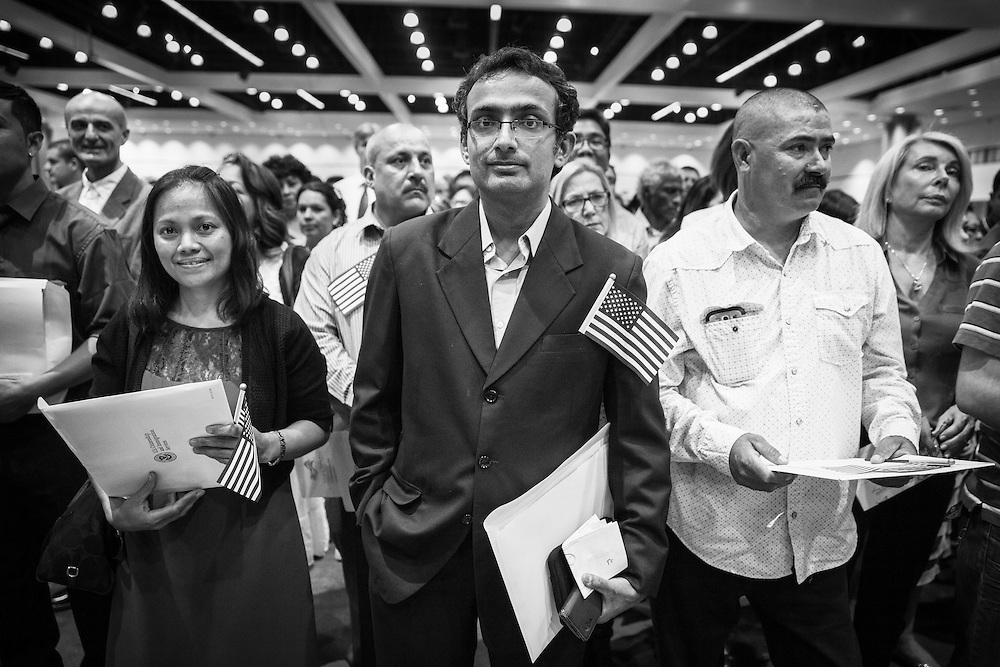 With certificates in hand, a group of new Americans wait to exit the hall to meet their friends and relatives.