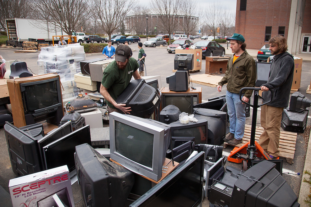 Jeremy Martin of Accurate IT Services, center, looks for a place to stack a television that was dropped off during the Electronics Recycling Day at Ohio University.  The program was part of Recyclemani and help add approximately 18,000 lbs. to the schools total.  Photo by Ohio University / Jonathan Adams