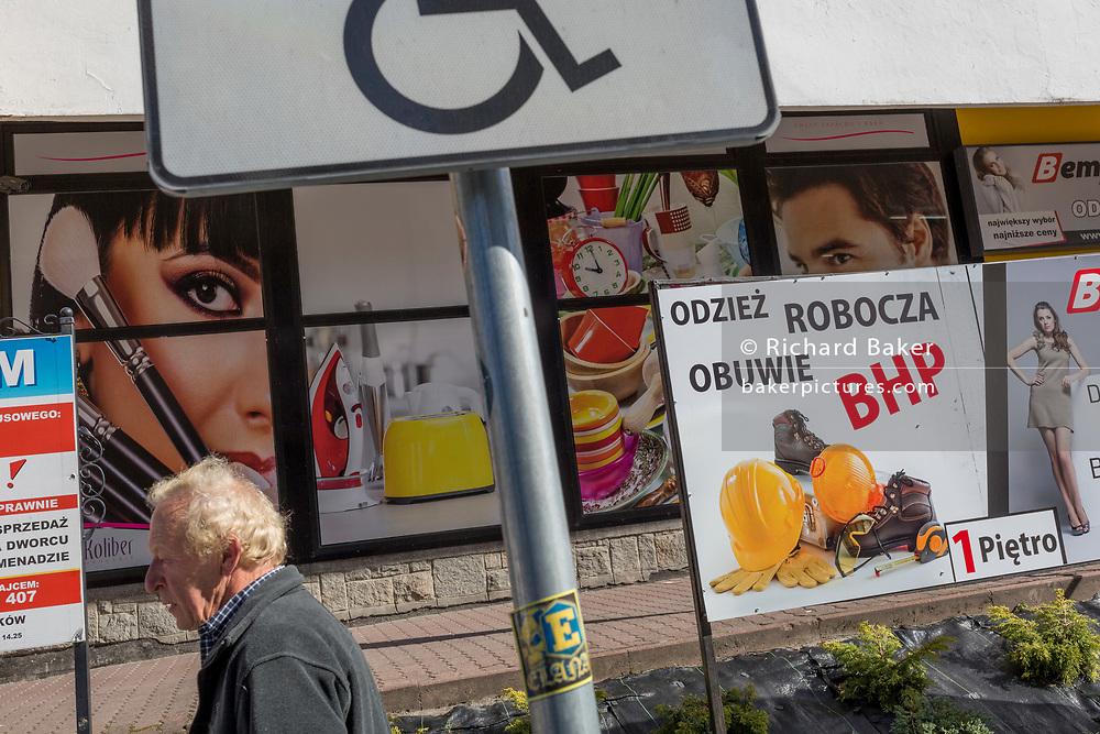 A Polish shopper walks past advertising signs, on 21st September 2019, in Szczawnica, Malopolska, Poland.