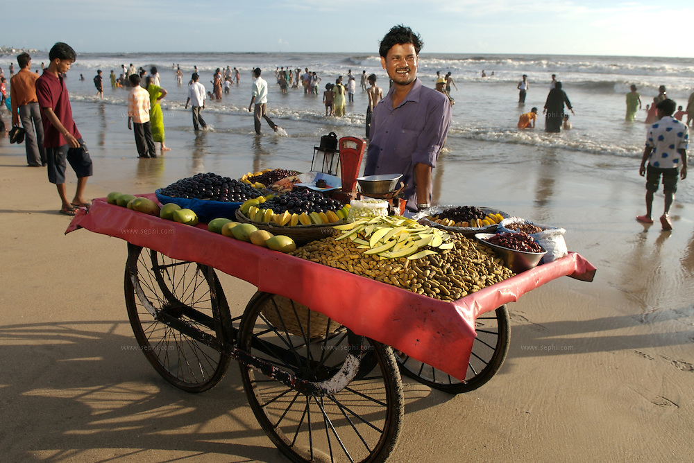 A fruit snack vendor, illuminated by a reflection of a near by hotel window, brings his cart almost to the water line. Juhu beach, Mumbai, June 2007