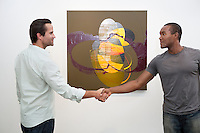 Two man in casuals shaking hands in front of wall painting