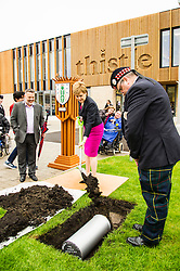 Pictured: Nicola Sturgeon braves the showers to bury the time capsule<br /> <br /> The First Minister Nicola Sturgeon, MSP, joined people supported by the Thistle Foundation to bury a time capsule to mark the opening of a new health and social care centre. <br /> Ger Harley | EEm 14 June 2016