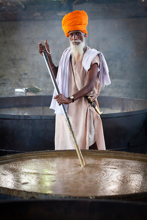 A cook in a Sikh kitchen cooking in an extremely large pot.<br /> The Sikh kitchen is part of the Golden Temple that provides tens of thousands of free meals on a daily basis.