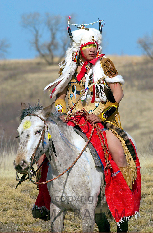 CANADIAN PLAINS INDIAN ON HORSEBACK WEARING A TRADITIONAL COSTUME AND HORNED HEAD-DRESS AT WANUSKEWIN HERITAGE PARK, SASKATOON, CANADA