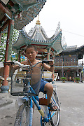 A boy on a bike at at an old temple in Wenzhou, Zhejiang, China.