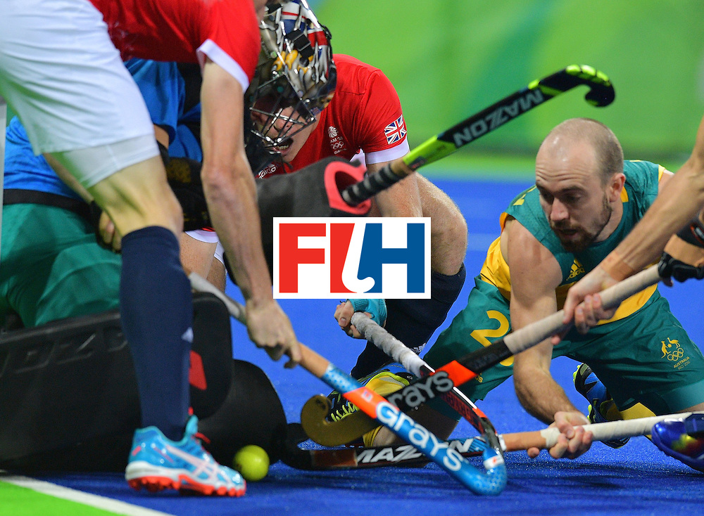 Australia's Matthew Swann (R) tries to help out Australia's goal keeper Andrew Charter during the men's field hockey Britain vs Australia match of the Rio 2016 Olympics Games at the Olympic Hockey Centre in Rio de Janeiro on August, 10 2016. / AFP / Carl DE SOUZA        (Photo credit should read CARL DE SOUZA/AFP/Getty Images)
