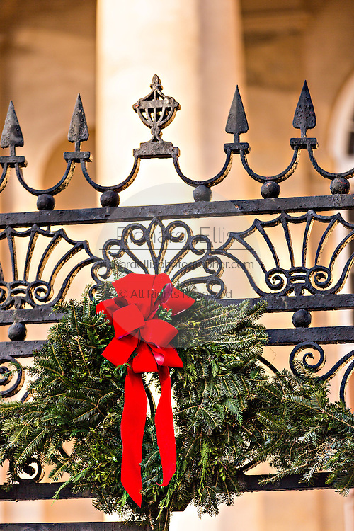 Iron gate decorated with a Christmas wreath in historic home Charleston, South Carolina.