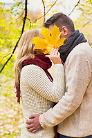 Portrait of Mature couple kissing in park while the woman is covering their face with maple leaf
