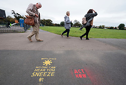 """© Licensed to London News Pictures; 09/09/2020; Clevedon, UK. Stencils are seen on the pathways by the Marine Lake advising people to keep social distancing during the coronavirus covid-19 pandemic. The stencils by North Somerset Council with their logo refer to cultural memes such as Star Trek """"Space the final frontier"""", the film Alien """"In Space no one can hear you sneeze"""", the song """"Don't Stand So Close To Me"""" by the Police and the world war one recruitment poster """"North Somerset needs you to keep your distance"""". Other stencils have been added referring to the climate crisis and global warming. Photo credit: Simon Chapman/LNP."""