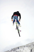 SHOT 2/9/13 1:50:07 PM - A competitor pulls a tailwhip during practice for the Best Trick Bike event at the second annual Winter Mountain Games presented by Eddie Bauer at Vail Ski Resort in Vail, Co. The Winter Mountain Games feature competitions in X-Country On-Snow Mountain Bike Races, mixed climbing, Telemark Big Air, Best Trick Bike and On-Snow Mountain Bike Crit with more than $60,000 in prize money on the line. (Photo by Marc Piscotty / © 2013)