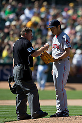 OAKLAND, CA - JUNE 22:  MLB umpire Greg Gibson #53 exchanges baseball with Koji Uehara #19 of the Boston Red Sox during the tenth inning against the Oakland Athletics at O.co Coliseum on June 22, 2014 in Oakland, California. The Boston Red Sox defeated the Oakland Athletics 7-6 in 10 innings.  (Photo by Jason O. Watson/Getty Images) *** Local Caption *** Greg Gibson; Koji Uehara