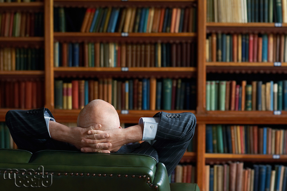 Businessman Sitting in Library hands behind head