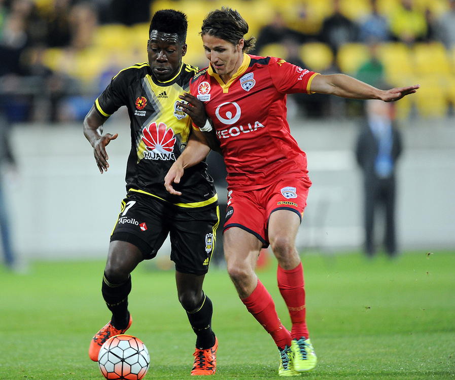 Phoenix's Jeffery Sarpong, left, contests the ball with Adelaide United's Michael Marrone in the A-League football match at Westpac Stadium, Wellington, New Zealand, Friday, November 13, 2015. Credit:SNPA / Ross Setford