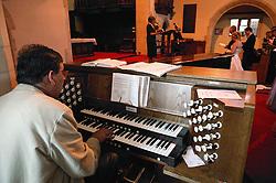 Church organist playing organ during wedding ceremony,