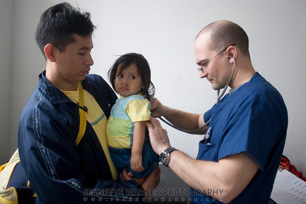 Edgar Ortíz holds his son of 15 months, also named Edgar, while Doctor Stephen Ball examines him, checking to make sure he is healthy enough to withstand the anesthesia during surgery.  The pair traveled from Santo Domingo to Otavalo, a trip of approximately 6 hours and had to break through a bussing strike in order to see if baby Edgar was available for surgery.  All the patients are pre-screened, but if a patient is has a cold, cough, or respitory infection, they are often told to come back the next year as it will be too dangerous to put them under.