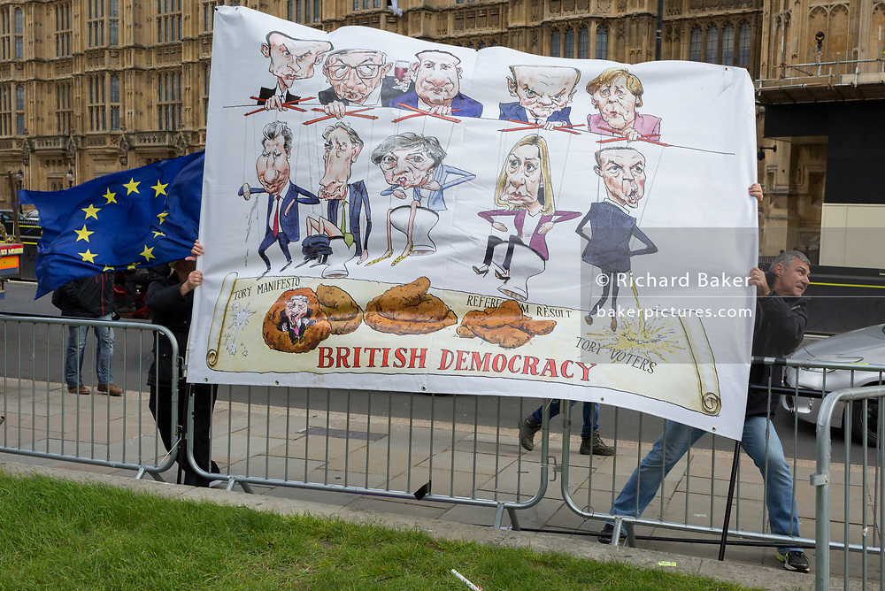 As Prime Minister Theresa May again meets opposition Labour leader Jreemy Corbyn in an attempt to break the deadlock in parliament of Brexit, Brexiteer protestors try to control a political satire banner in strong winds opposite parliament in Westminster, on 4th April 2019, in London, England.