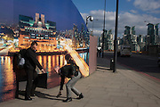 A kind stranger picks-up a hat belonging to another pedestrian in front of a construction hoarding - a night time panorama of the Thames south bank, featuring the HQ of the intelligence service (MI6) across the river in Vauxhall.