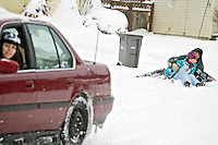 "Jayden Requena, 18, keeps an eye on her ""hookybobbin"" team that fell off their sled while she was towing them  behind her car Friday. Evan Puskash, 15, and Faith Nelson, 10, used their snow day away from school to their advantage by being pulled around their Coeur d'Alene neighborhood with hot chocolate breaks between sessions."