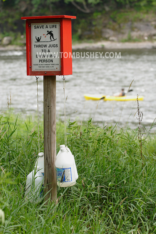 Mongaup Valley, NY - Jugs used to help swimmers in trouble hang from a post by the Delaware River on Aug. 9, 2007. A kayaker is moving down the river in the background..