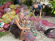 """Eco-pioneer Richard """"Rishi"""" Sowa designed and built an artificial island kept afloat by 100,000 plastic bottles.<br /> <br /> Spiral Island II is actually Rishi Sowa's second artificial island. He built the first one in 1998, near Puerto Aventuras, using 250,000 plastic bottles to keep it afloat. Sadly, his recycled island was destroyed in 2005, when Hurricane Emily passed through the area. Most of Spiral Island was washed up on the beach, but Sowa decided to build a whole new island, in a safer area.<br /> <br /> And that's how Spiral Island II came to be. With the help of volunteers, Rishi Sowa gathered around 100,000 plastic bottles and hand-built his second recycled island, in a lagoon that offers protection from bad weather. The new island features a house, beaches, 2 ponds and a solar-powered waterfall, but its creator says Spiral Island II is and always will be an eco-work-in-progress. Although smaller than its predecessor (only 20 meters in diameter), you can expect the new Spiral Island to increase in size, significantly.<br /> <br /> One of the most impressive DIY projects ever attempted, Spiral Island has inspired volunteers to come to Mexico and help Rishi Sowa improve his creation. But while some believe it a perfect environmental design, built entirely of recycled materials, there is some controversy surrounding Spiral Island. There are those who believe that if the island gets destroyed by a hurricane, again, the materials used to build it (mainly plastic bottles, sand, mangrove plants) will litter the waters of the Atlantic.<br /> Photo Shows: Two British Workers help with the Build<br /> ©Spiral Island /Exclusivepix"""