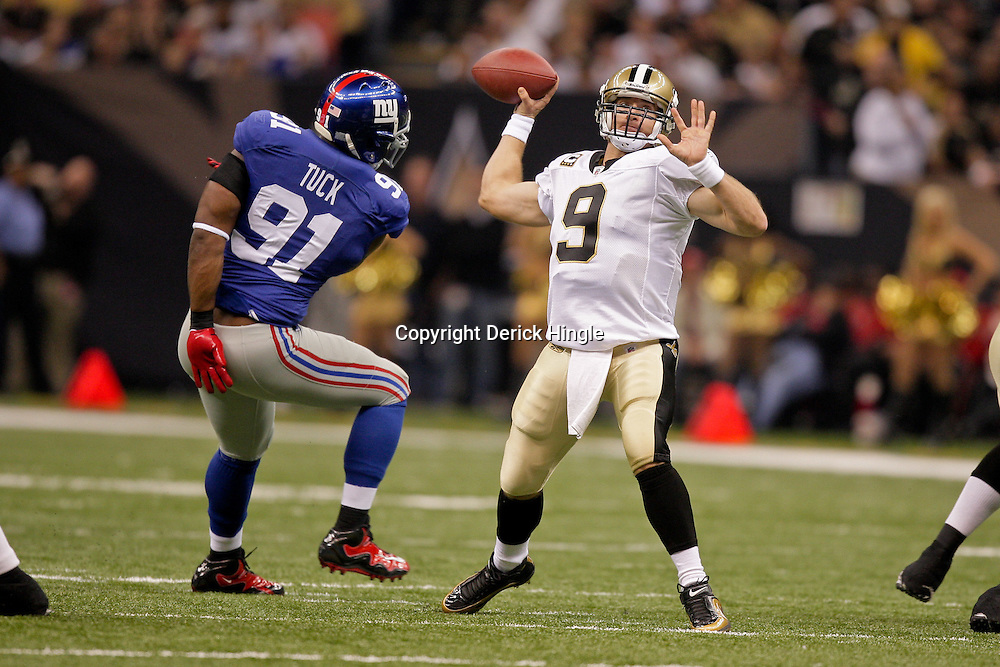 2009 October 18: New Orleans Saints quarterback Drew Brees (9) throws as New York Giants defensive end Justin Tuck (91) provides pressure during a 48-27 win by the New Orleans Saints over the New York Giants at the Louisiana Superdome in New Orleans, Louisiana.
