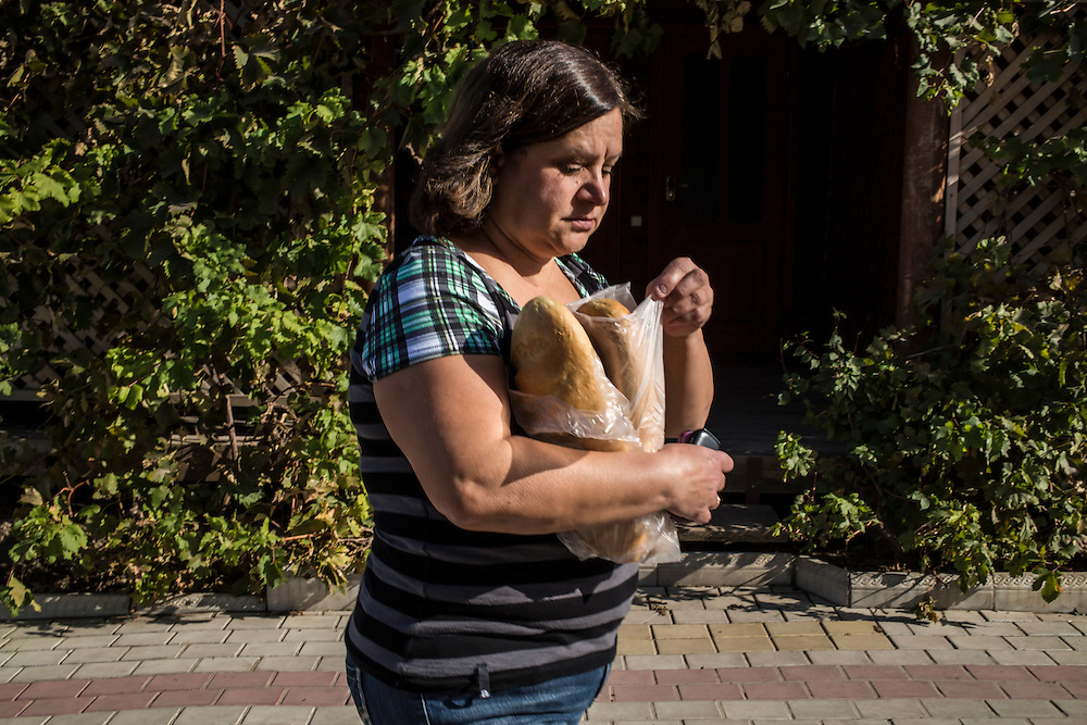 A woman, part of a group of internally displaced people who fled the besieged city of Donetsk and are now living in a small seaside resort that has become their home, carries bread on Tuesday, October 14, 2014 in Berdyansk, Ukraine. Photo by Brendan Hoffman, Freelance