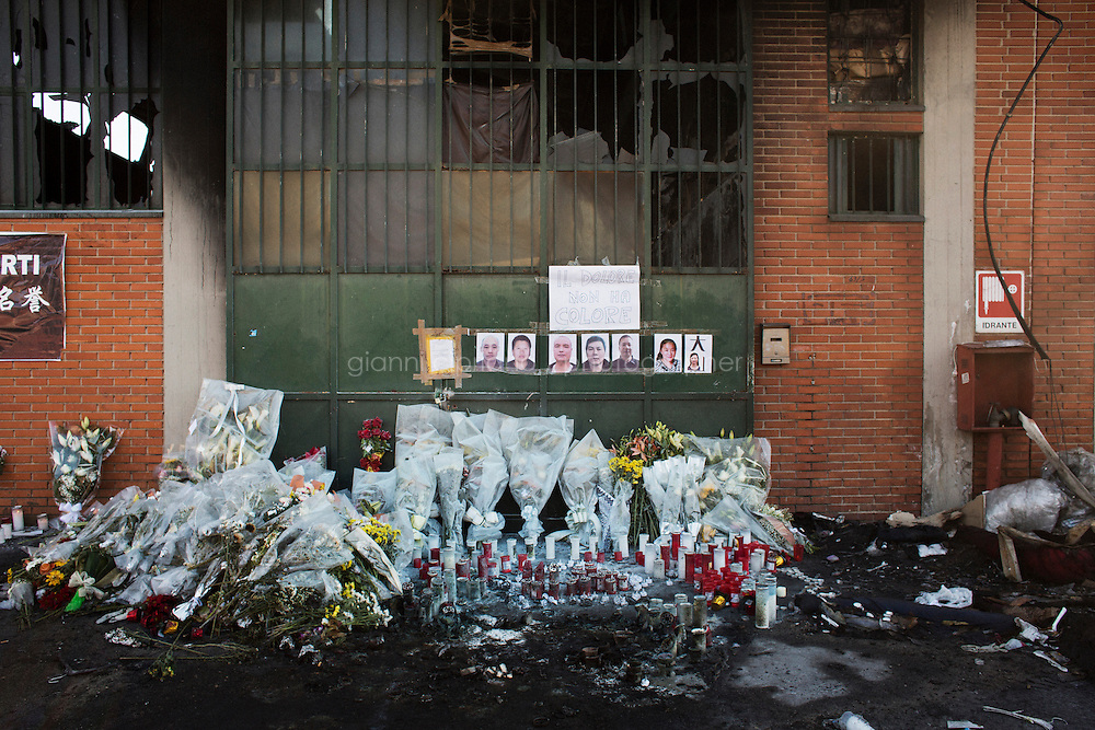 PRATO, ITALY - 4 December 2013: Candles and flowers are left outside the fast fashion outlet &quot;Pronto Moda Teresa&quot;, under the seven photographs of Chinese workers who died after a fire swept through on Sunday, in Prato, Italy, on December 4th 2013. Other two Chinese workers were badly injured.<br /> <br /> The city of Prato has the largest concentration of Chinese in Europe, as well as having the second largest population of Chinese people overall in Italy, after Milan. The Chinese who have come to Prato since the late 1980s have transformed the city and its centuries-old textile industry.