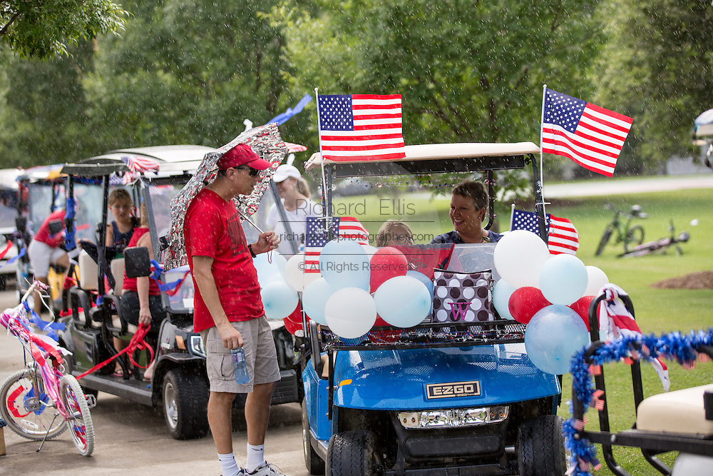 Residents of Daniel Island wait out a summer rain storm as they celebrate Independence Day early with a bicycle and golf cart parade July 3, 2013 in Charleston, SC.