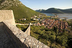 Europe, Croatia, Dalmatia, Mali Ston.  Salt pans, lush hills and village of Mali Ston, viewed from walls of 15th century fort.