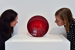 "© Licensed to London News Pictures. 12/10/2017. London, UK.  Staff members view ""Red Lens For Grenfell"", 2017, by Anish Kapoor (Est. GBP20-30k) at a preview of artworks for the ""Art for Grenfell"" auction taking place at Sotheby's, New Bond Street, on 16 October.  Leading contemporary artists have agreed to donate works to the auction, the proceeds of which will be divided equally amongst the 158 surviving families of the Grenfell Tower fire by the Rugby Portobello Trust charity. Photo credit : Stephen Chung/LNP"