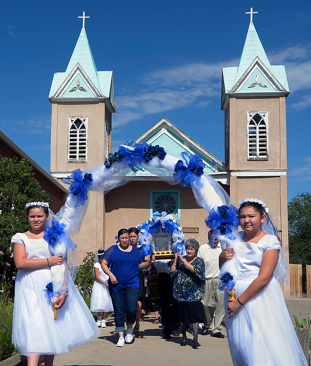 gbs081017i/RIO-WEST -- Fatima Trujillo, left, and Jovanna Montoya, right, carry an arch as Erica Cordova, Margaret Montoya and Ruth Lopez, from left, carry a picture of San Lorenzo from the Santurio de San Lorenzo into Our Lady of Sorrows Catholic Church during Las Fiestas de San Lorenzo on Thursday, August 10, 2017.(Greg Sorber/Albuquerque Journal)