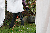 Mowing the lawn beside a clothes line with bed linen