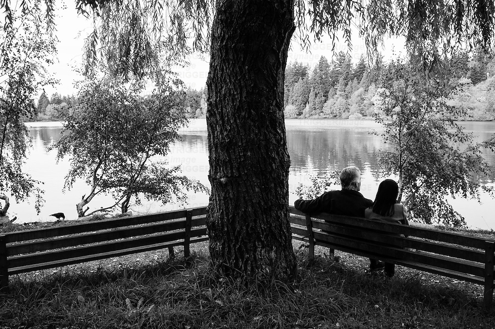 A couple sitting on a park bench with trees and reflections in a lagoon.